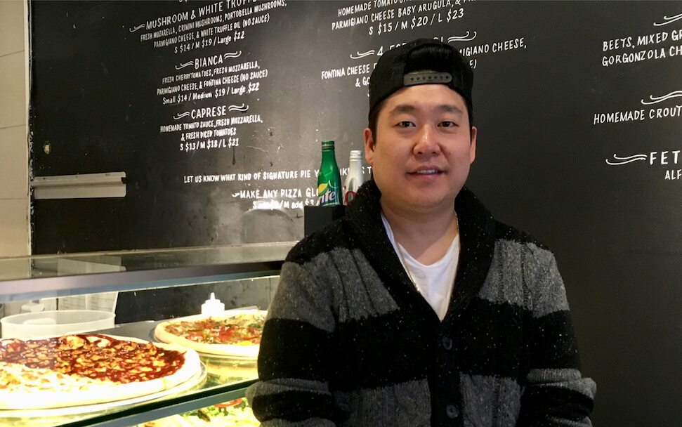 Portrait of the Lean Crust pizza shop owner wearing a black and white striped sweater and a black baseball cap on backwards with pizzas behind him in a case and black wall with white writing describing the menu.