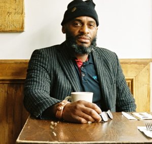 Michael Thompson, owner of Brooklyn Moon, sitting at a table and looking at the camera wearing a striped blazer and a black knit hat.
