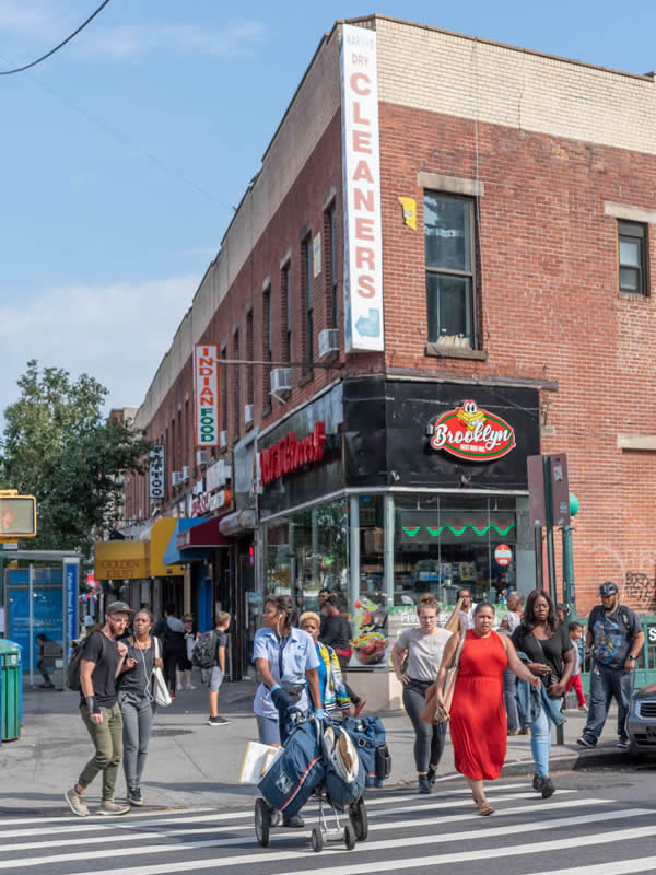 A group of people crossing the street at a Brooklyn intersection on a summer day showing several businesses in the background including a dry cleaner and an Indian restaurant.