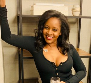 Sabrina Carson, owner of The Nail Boutique, posed and smiling, with shelves in the background.