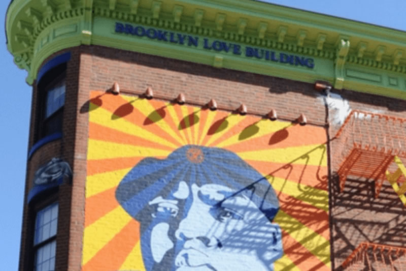 Detail of the Brooklyn Love Building with a colorful mural painted featuring a portrait of rapper Biggie Smalls on the brick facade.