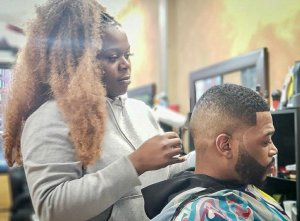 Barber Yohnee Miller with client cutting hair