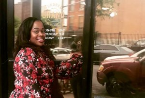 Yohnee Miller in front of Hundred Grand Barbershop