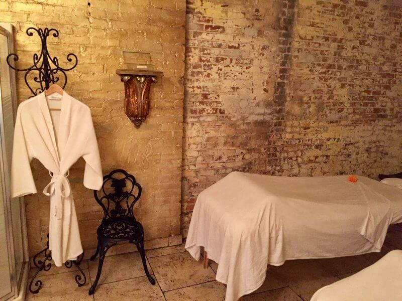 spa room with robe hanging and massage table nearby