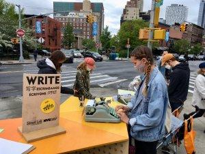 Woman using typewriter at Street Lab desk on Fulton Street