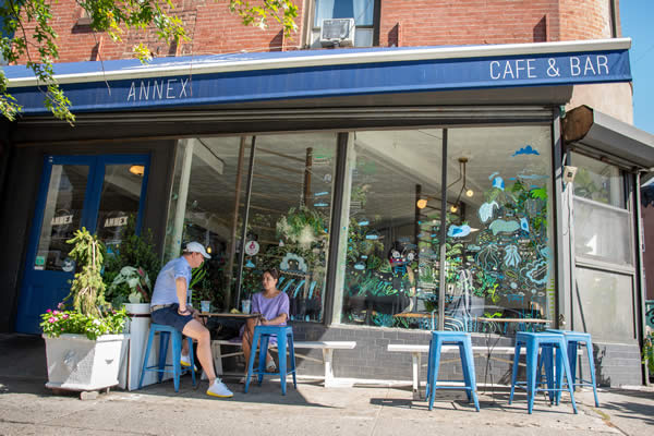 An exterior view of the Greene Grape annex with a blue awning that reads Annex Cafe and Bar in white with blue painted metal stools with two people sitting at an outdoor table having a drink.