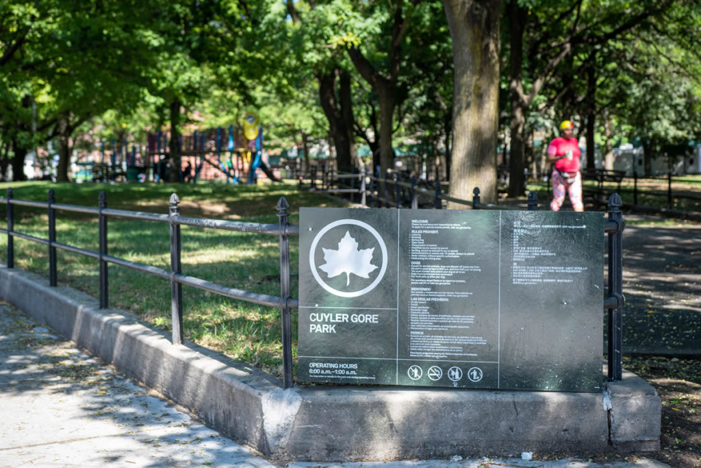 A green sign with a giant white maple leaf in a circle over the name Cuyler Gore Park on a black iron fence in the foreground with a park and person walking in the background on a summer day.