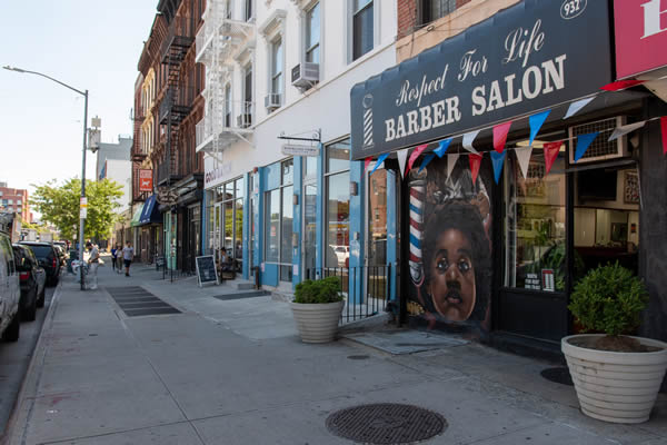 Sidewalk view of Respect for Life Barber Salon in foreground in Clinton Hill.