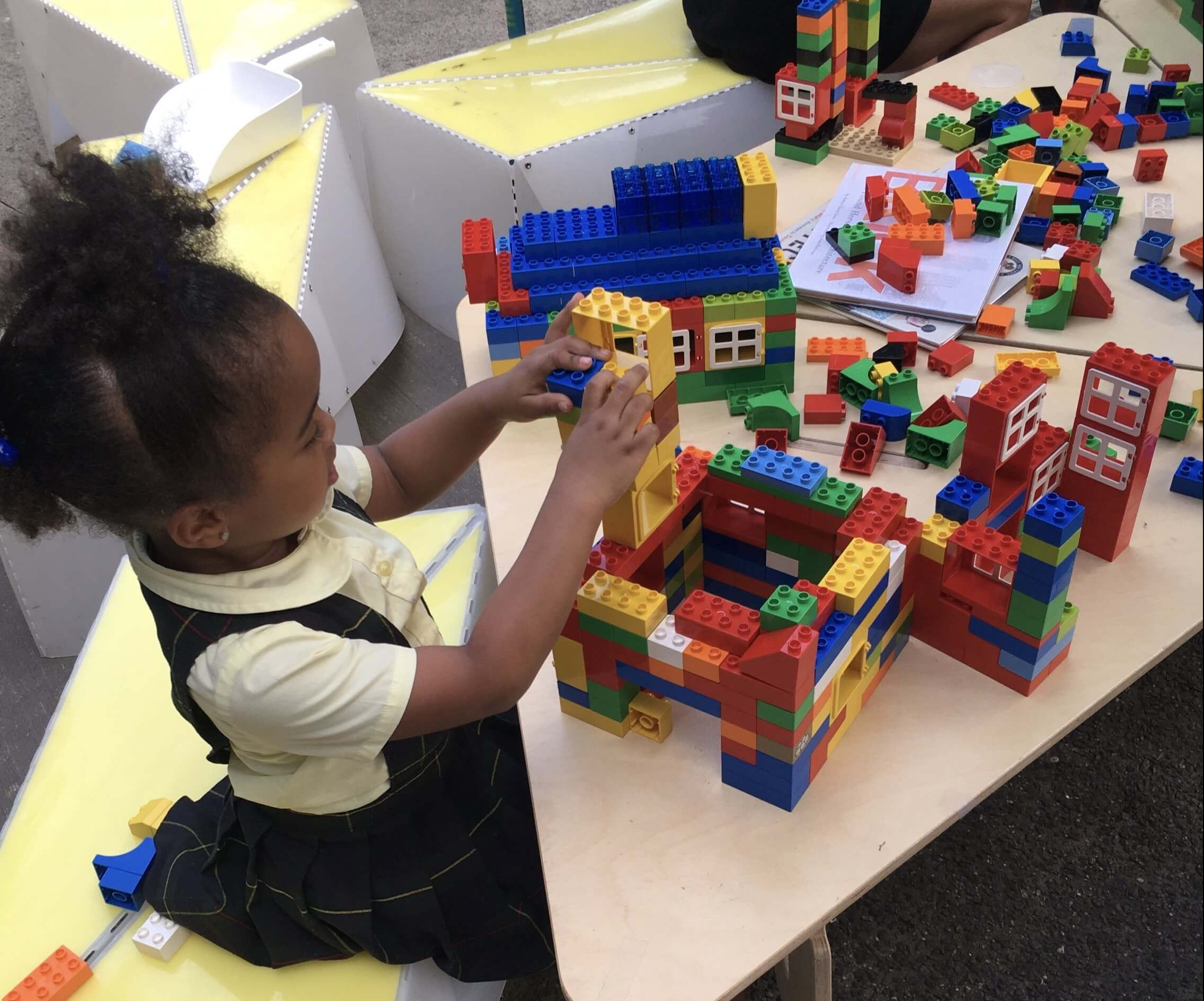 Little girl seated building with LEGO bricks